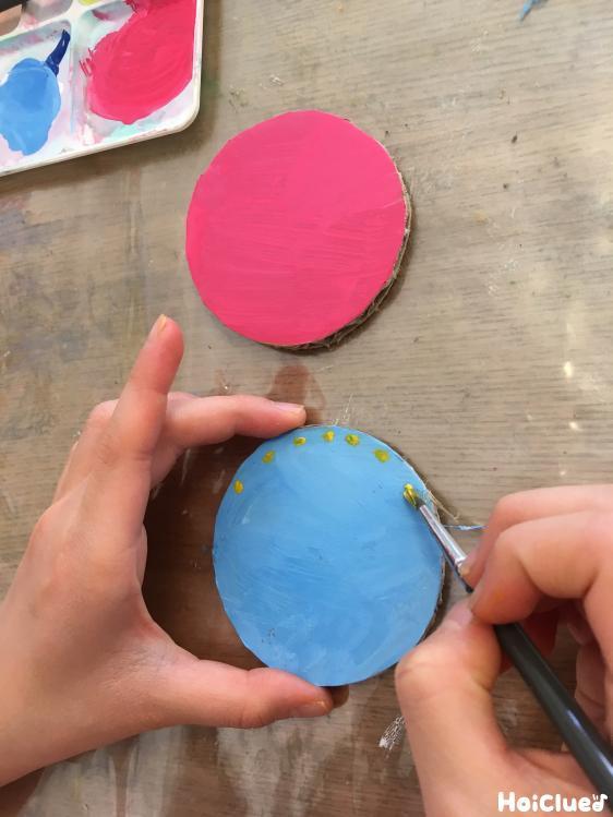 丸いダンボールに色付けしている写真