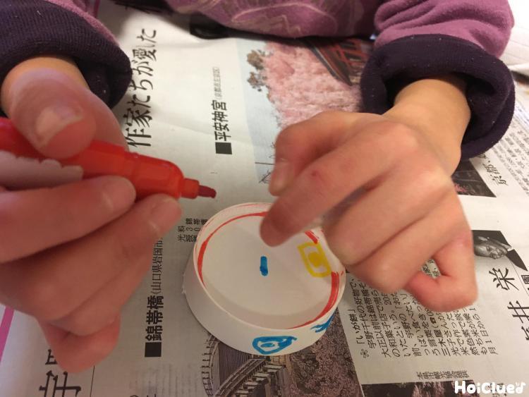 紙コップの底を切り取り文字盤を描いている様子
