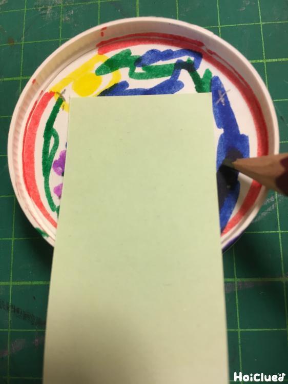 紙コップの底に細く切った画用紙をあてている様子