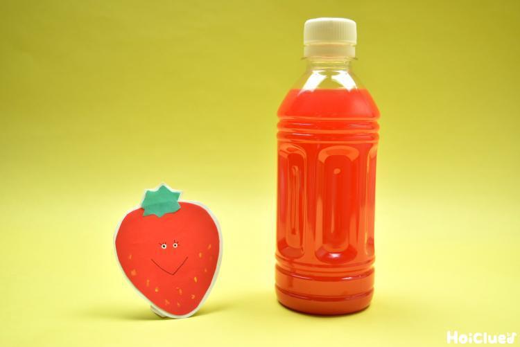 いちごと赤い水の入ったペットボトルの写真
