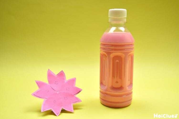 桜とピンク色の水の入ったペットボトルの写真