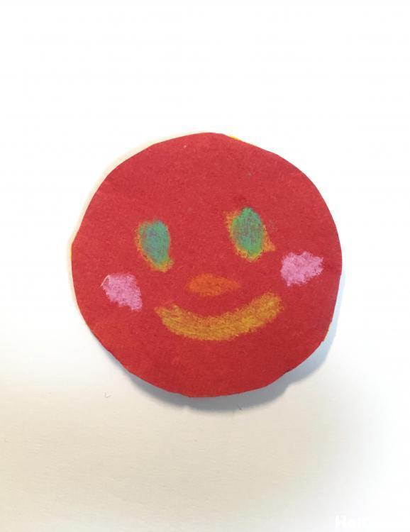 丸く切った色画用紙に顔を描いた写真