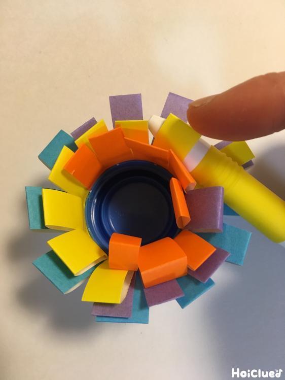色とりどりの色紙をペットボトルキャップに巻きつけている写真