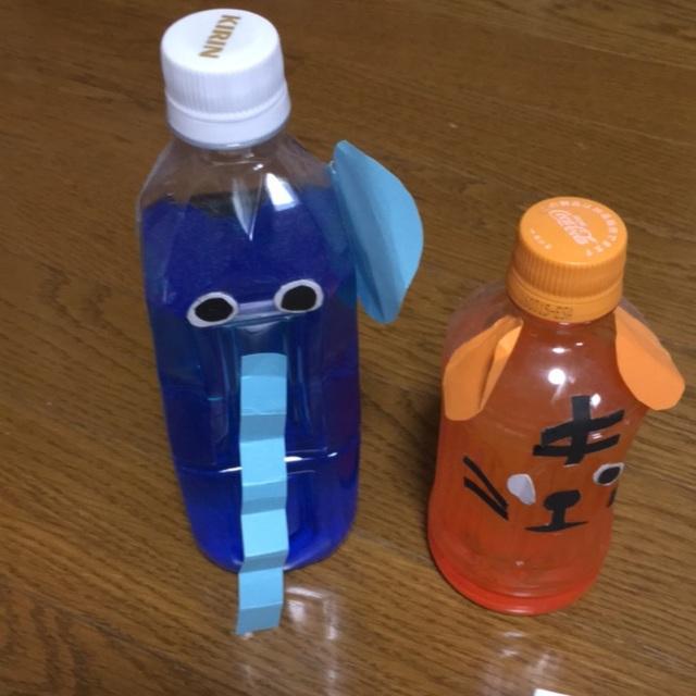【アプリ投稿】・自分の好きな動物を決める。・色画用紙で耳や鼻、口などを作る。・両面テープで切った画用紙をペットボトルとくっつける。・絵の具で色をつくる。⇨〔水をペットボトルの八分目まで入れ、絵の具を垂らしてからキャップを閉める。そしてペットボトルを振る。〕・黒目の部分はボンドを使って貼る。