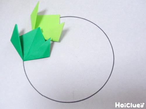 丸い線の上に折り紙を置いている写真