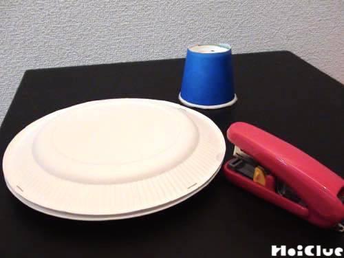 中表に合わせた紙皿をホッチキスで留めている様子