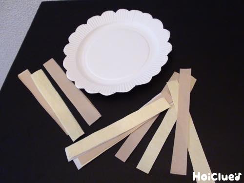 花形の紙皿と細長く切った折り紙の写真