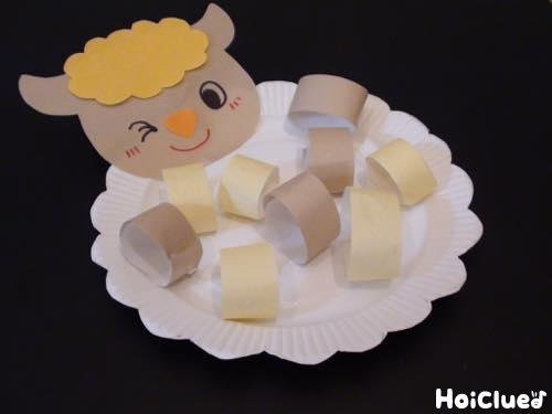 顔を描いた羊と輪っかを紙皿に貼った写真