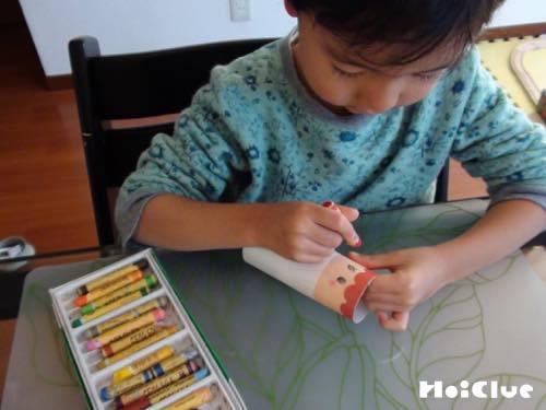 トイレットペーパーの芯に顔を描く子どもの様子