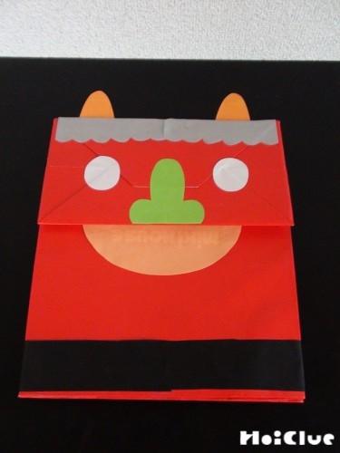 袋に鬼の顔のパーツを貼り付けた写真