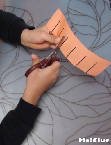 オレンジの細長い画用紙に切り込みを入れている写真
