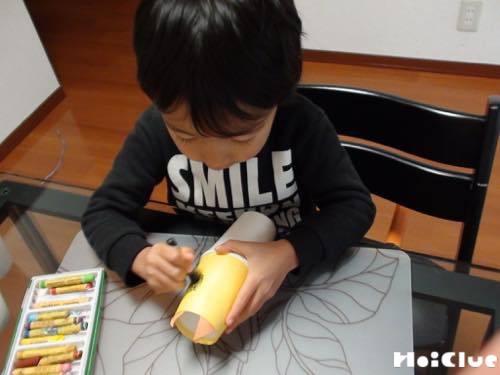 貼り合わせた紙コップに絵を描く子どもの様子