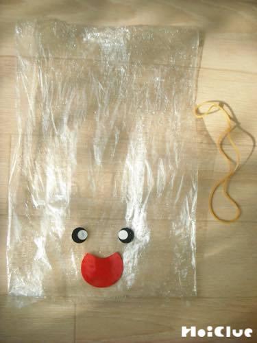 顔のパーツを貼ったビニール袋と輪ゴムの写真