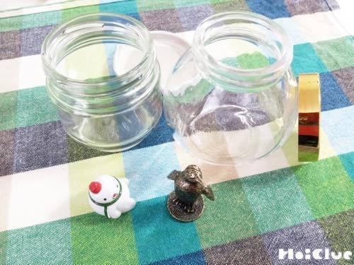 空き瓶と中に入れる小さな置き物の写真