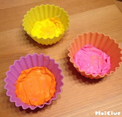 シリコンカップに色のついた紙を入れている写真