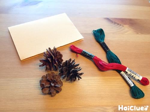画用紙、松ぼっくり、刺繍糸の写真