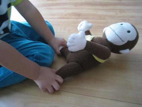 猿のぬいぐるみの足を持つ子どもの写真