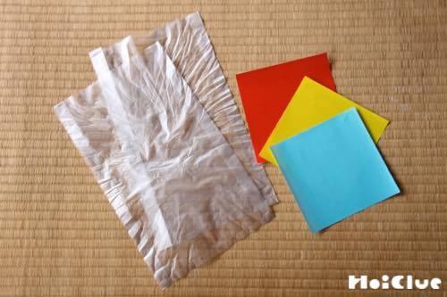 ビニール袋2枚と3色の折り紙の写真