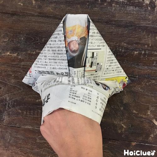 折った新聞紙に手を入れる写真