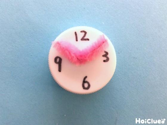 ペットボトルキャップにモール差し込み時計の針を作った写真