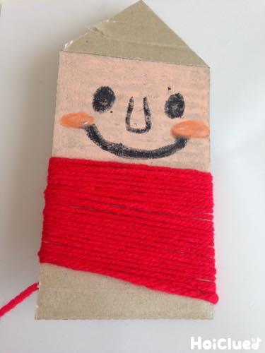 切ったダンボールに赤い毛糸を巻きつけている写真