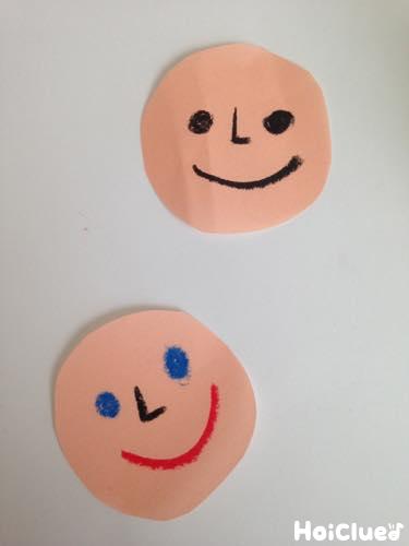 丸く切った画用紙に顔を描いた写真