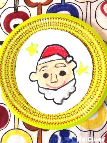 サンタの絵を描いた画用紙を紙皿に貼った写真