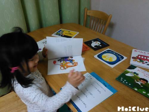 ヒントを見ながら絵本を広げてキャラクターを探す子どもの様子