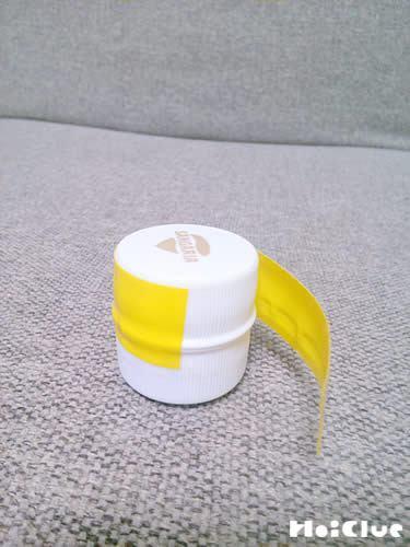 フタをするように2個のペットボトルキャップをテープで留める様子