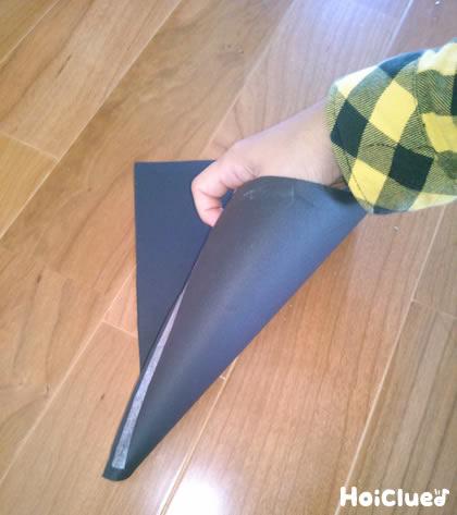画用紙を円錐形に丸める様子