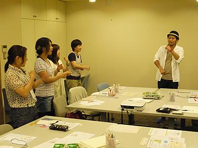 参加者に「おおきなカブ」の遊び歌を教える矢生さんの写真