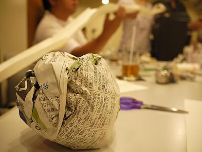 新聞を丸めたボールと長い滑り台を支える参加者の様子
