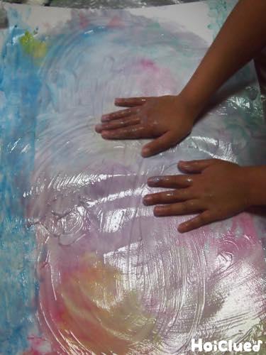 手の平で画用紙に絵の具をのばす様子