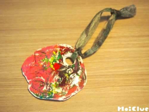 絵の具で色を塗り開けた穴にリボンを通し完成したオーナメント