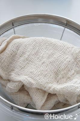 豆腐をさらし布で包み込んでいる写真