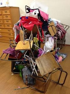 高く積み上げられた椅子やカバンなどの写真