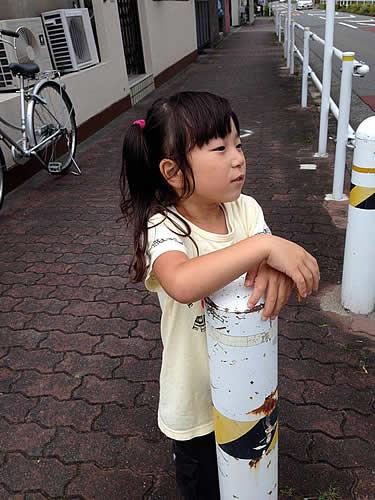 道端のポールに手を乗せる女の子の写真