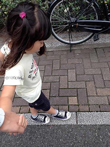 道路に引かれた線の上を歩く女の子の写真