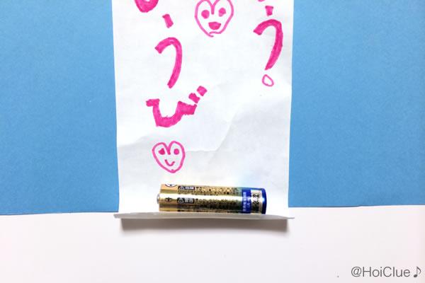 乾電池をメッセージを書いた紙の端に乗せて貼り付けている写真