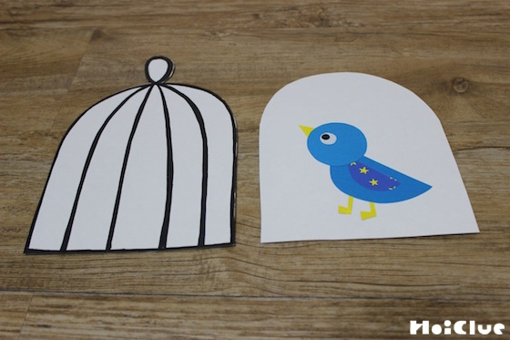 厚紙で作った鳥かご型に1枚はかご模樣を描き、もう1枚は鳥を貼った写真