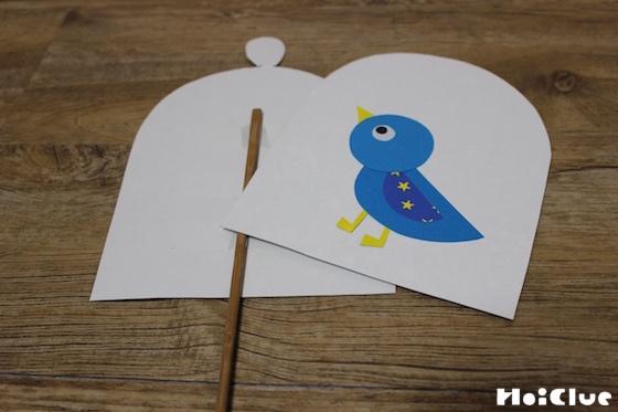 割り箸に2枚の鳥かごを貼り合わせる様子