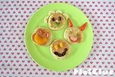 フルーツをパンケーキの上の乗せ動物などの顔にした写真