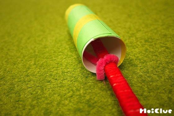 トイレットペーパーの芯の内側に貼り付けたモールを割り箸に巻き固定する様子