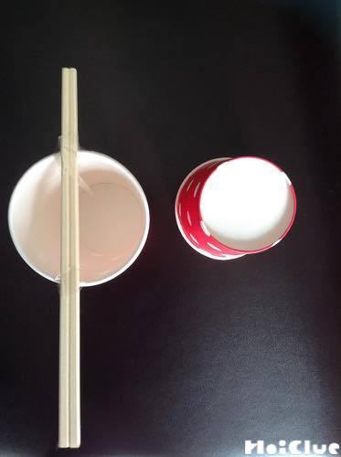 紙コップの上に置いた割り箸をセロハンテープで固定している様子