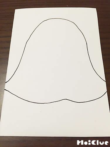 折ったコピー用紙におばけの絵を描く様子