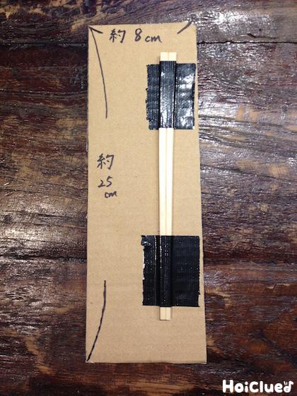 25㎝×8㎝に切った段ボールの右側に割り箸を貼った写真