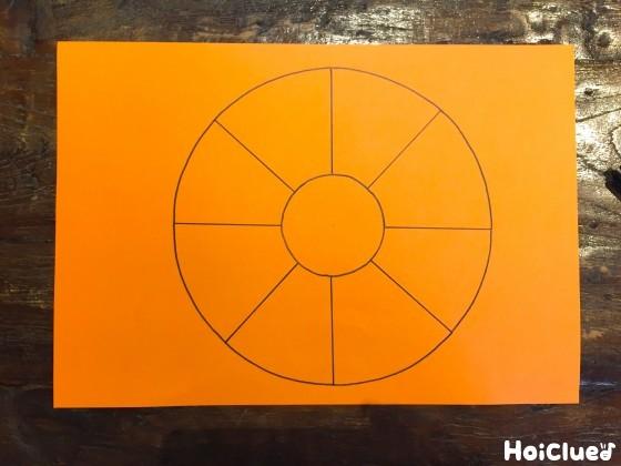 オレンジ色の画用紙に線を描いた写真