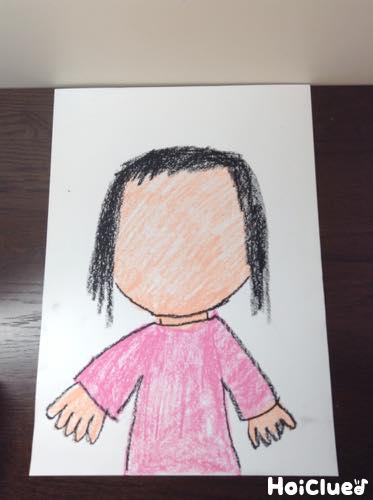 画用紙に目・鼻・口の無い顔と体を大きく描いた写真
