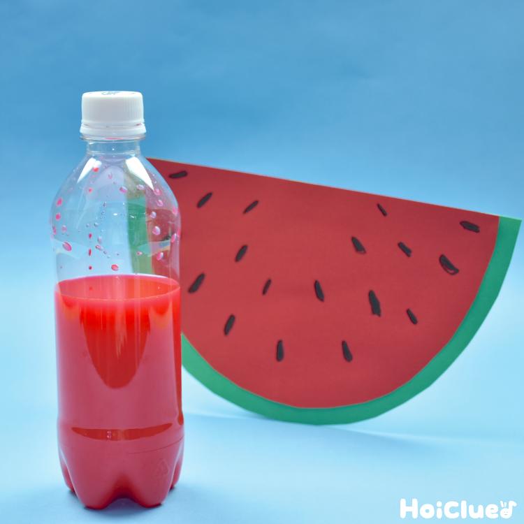 赤い水の入ったペットボトルと画用紙のスイカ