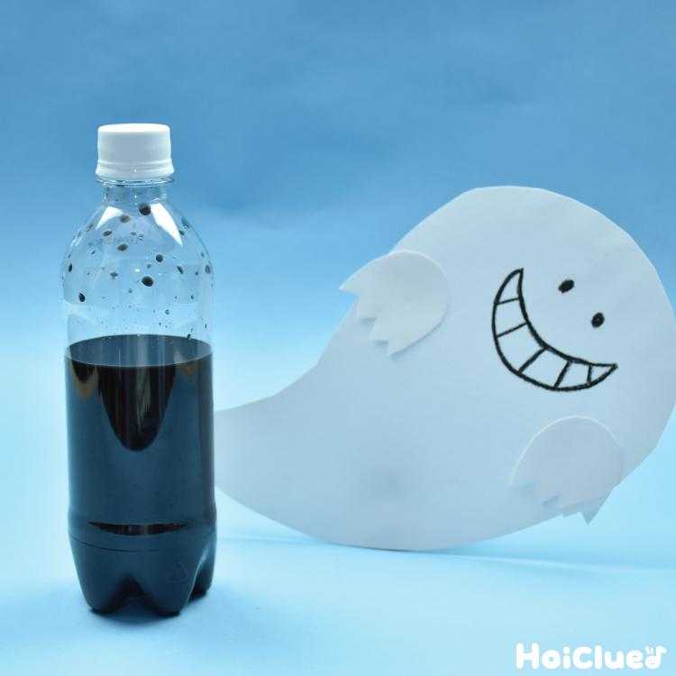 黒い水の入ったペットボトルと画用紙のおばけ